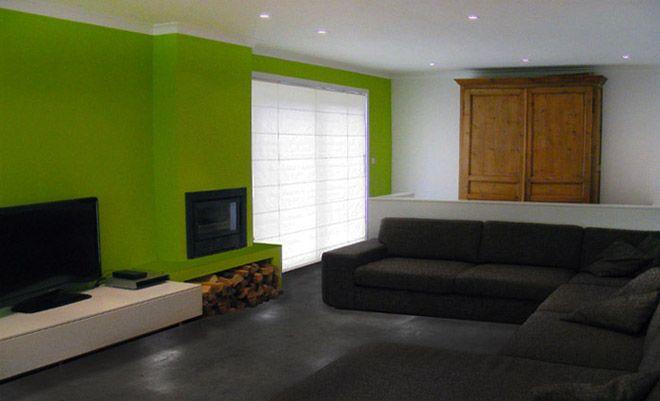 moderne woonkamer indeling en inrichting met groene accentwand en scheidingswand tussen bureau en zetel