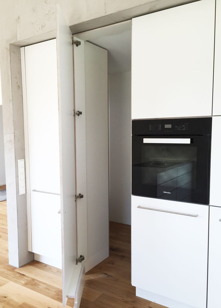 Weiße Küche mit integrierter, versteckter Speisekammer. Deckenhohe Schränke, Edelstahlgriffe und TipOn-System. | modern | elegant | Beton | individuell | Schreinerküche | Designerküche