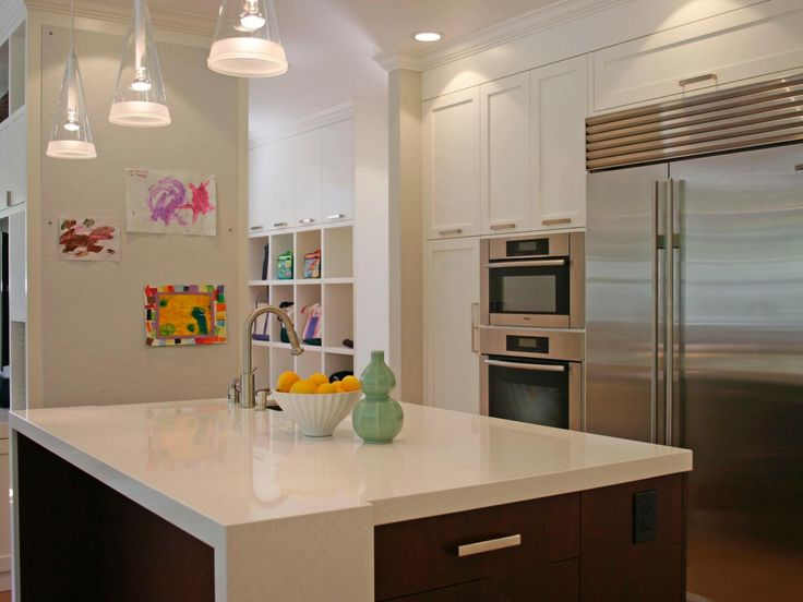 A white countertop protects the top and corners of an island from daily dents and dings in this contemporary kitchen. In addition to the cabinets above the double ovens, cubby hole shelves provide extra storage that's perfect for lunch boxes and backpacks.