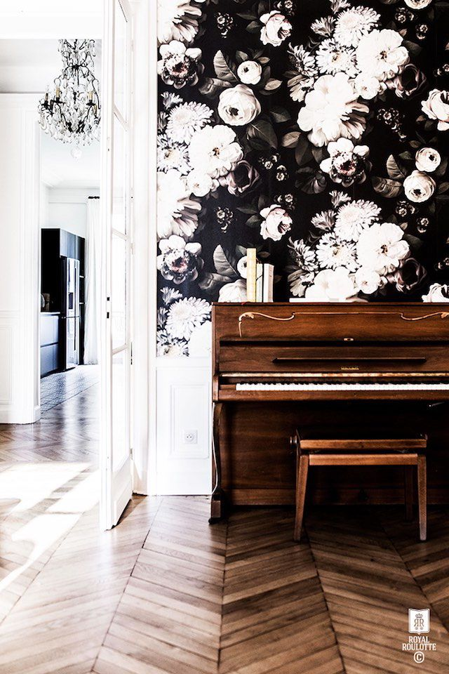 Piano against a bold floral wall.