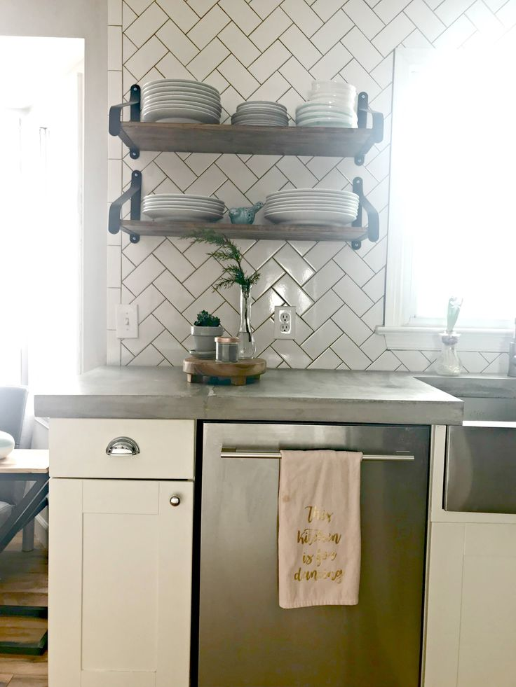 Herringbone subway title backsplash with charcoal grout.  I love how the wood shelves play off the concrete countertops.