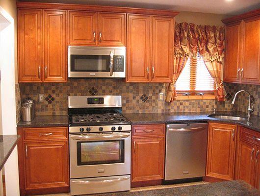 beautiful oak cabinets with dark granite countertops and