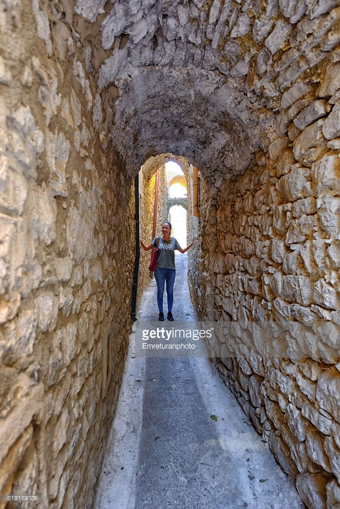 pyrgi is a medieval historic town in chios island,greece .it is a unesco world heritage site due its buildings with fantastic geometrical decorations .seen here is a typical narrow Street with a young smiling lady showing just how narrow the streets are between the houses are.