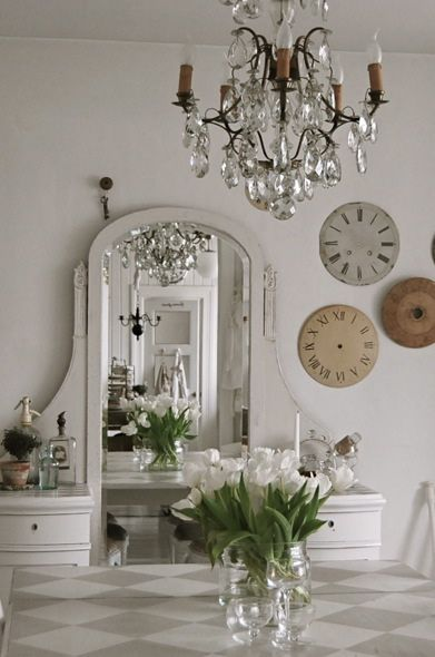 Vintage white mirror + old crystal chandelier + sepia clock faces = LOVE