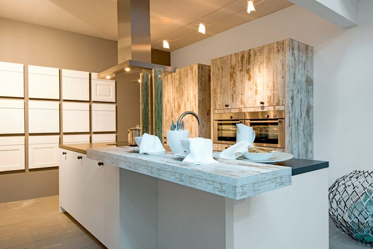 Moderne keuken met witte keukenkasten en houten accenten. De bekleding van de keukentoestellen zijn voorzien van bleek hout met witte strepen waardoor deze perfect past bij de witte keukenkasten en muren.