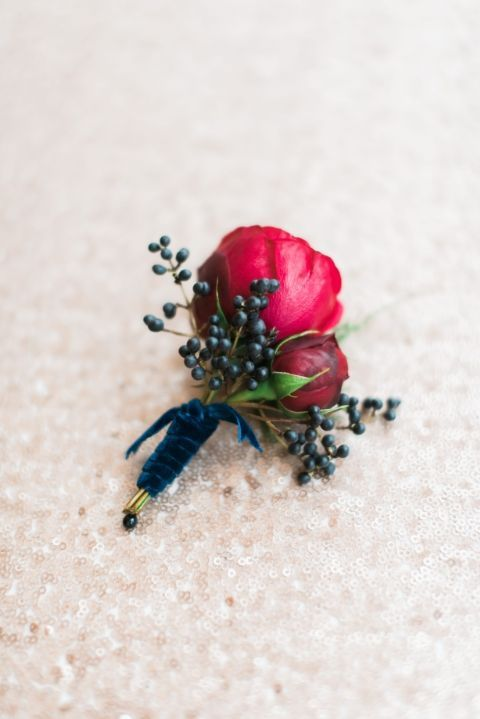 If the groom isn't a fan of navy blue suits, add a subtle hint of the color by wrapping a navy blue ribbon around the boutonnière.