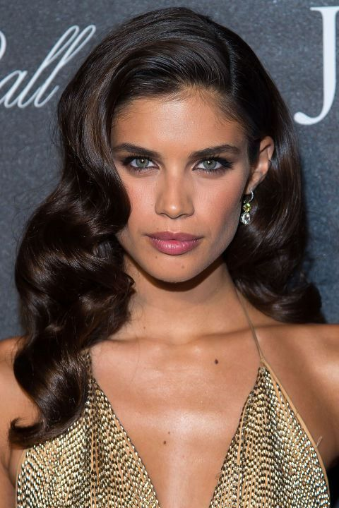 Sarah Sampaio Wearing Disco Glitz. The model brought '70s glamout to the Angel Ball with a plunging gold neckline, darky-lined eyes and big, disco waves like the ones seen on the Spring 2016 Runways.