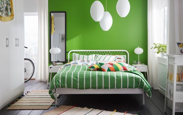 A small bedroom furnished with a bed for two in white metal with square patterned metal bars in the headboard. Shown together with white/green striped bedlinen and colourful extra cushions.
