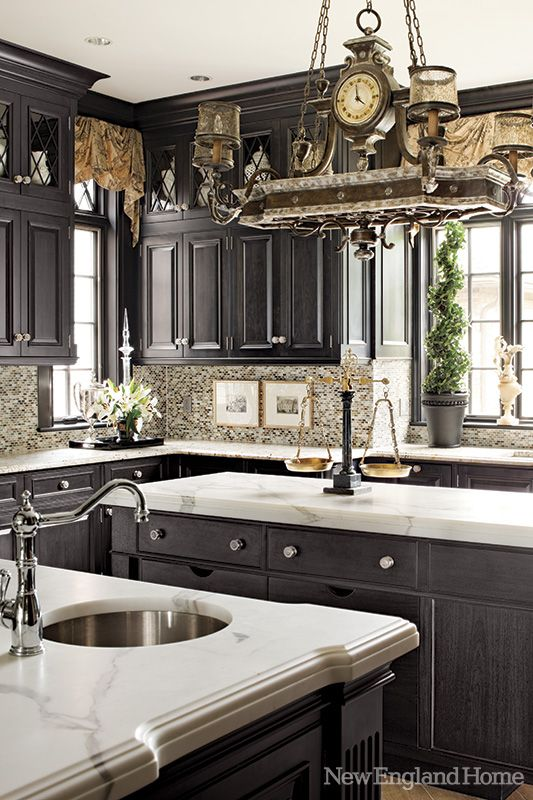 Dark gray cabinetry contrasts with Calcutta gold marble.