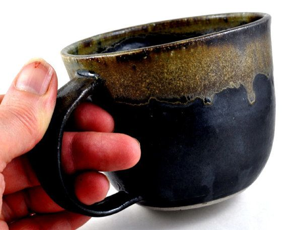 This handmade pottery ceramic coffee cup and is ideal for coffee, soup, milo, hot chocolate....anything.... The mug is wheelthrown and glazed in a matt black glaze, with the rim dipped in a contrasting neutral glaze which finishes with a beautiful feathered sheen to the rim.  The mug also features a generous handle suitable to the largest (or smallest) hands!  This coffee cup is a one of a kind handmade piece of tableware, sure to add style to your home décor, and is the ideal gift for a…