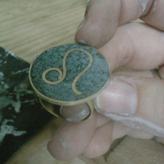Realizando acabados de anillo reconstituido con piedras de malaquita con hilo incrustado. Silvia Tapia.