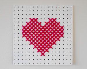 Een groot stuk gaatjesboard kun je veranderen in een zelfgemaakt XL-schilderij voor je Valentijn, voor Moederdag of zomaar als lief gebaar. Simpel geborduurd met grote kruissteken, voor een warm effect. En met het hart-patroon hieronder is borduren een makkie. Snel aan de slag!
