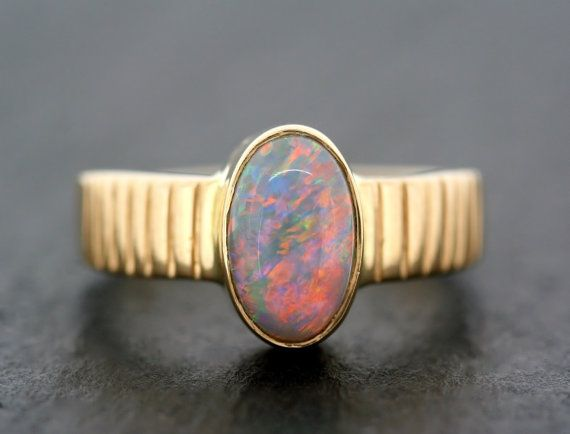 A simple vintage opal ring from the 1960s with a lovely, colourful stone. Made from 18ct gold with heavy patterned shoulders, this ring is set
