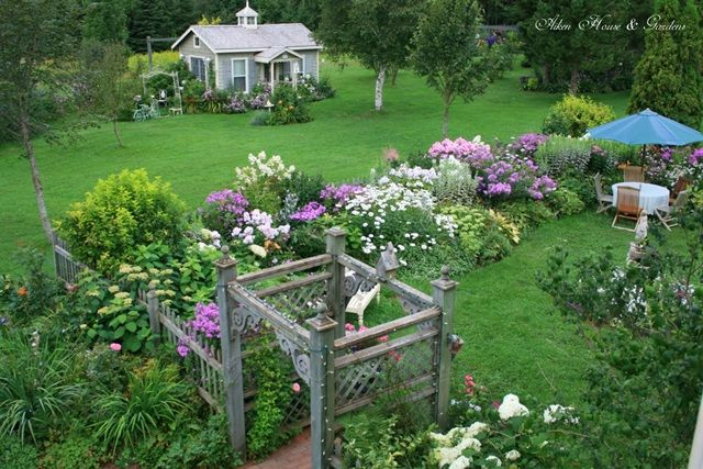 Summer Garden with Guest Cottage -- loving this arbor from Aiken Home and Gardens.