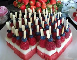 One of the most attractive fruit displays is this watermelon, honeydew, rasberry and blueberry fruit skewers. This would be perfect on 4th July for America's Independence Day