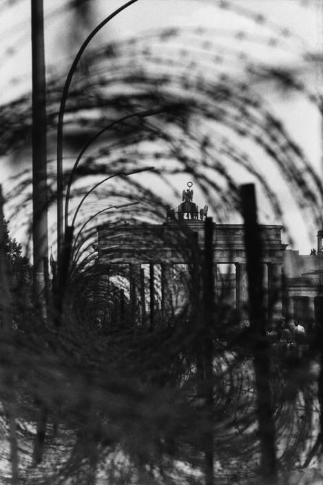 Rene Burri: Barbed wire along the Berlin Wall, 1957. The Brandenburg Gate (built 1788-91) can be seen in the distance.