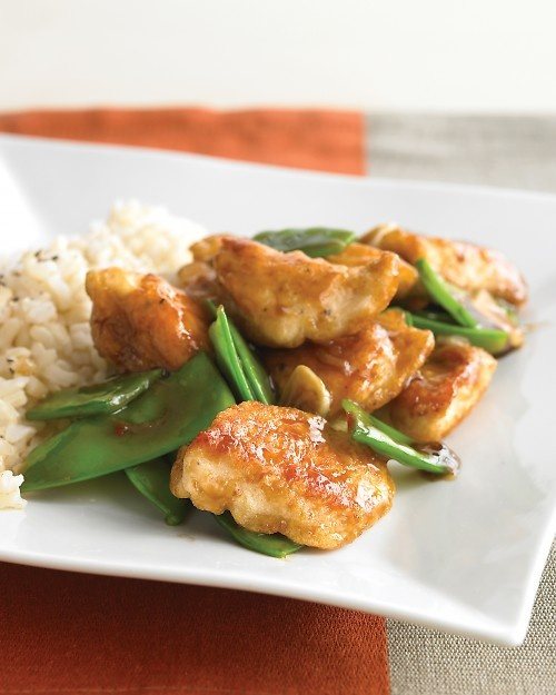 Lighter General Tso's Chicken  1 1/4 cups long-grain brown rice  1/4 cup cornstarch  1 pound snow peas, trimmed and halved crosswise  4 garlic cloves, sliced  2 teaspoons fresh ginger, grated and peeled  3 tablespoons light-brown sugar  2 tablespoons soy sauce  1/2 teaspoon red-pepper flakes  2 large egg whites  Coarse salt and ground pepper  1 pound boneless, skinless chicken breasts, cut into 1-inch pieces  2 tablespoons vegetable oil, such as safflower