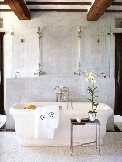 tub sits in front of a knee wall clad in Cararra marble with a view of the exposed shower system on the wall behind. love side table too
