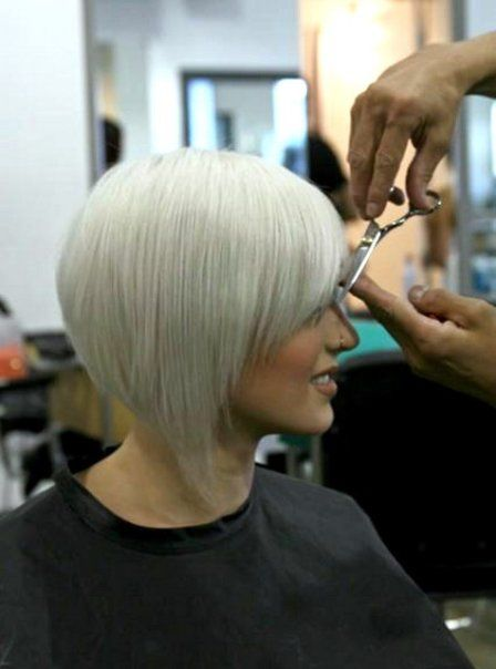inverted, stacked bob/wedge cut with side-swept bangs. platinum/silver color.