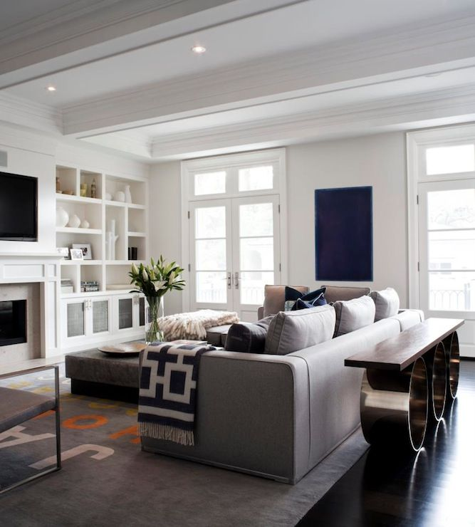 Chic, elegant living room with white built-ins flanking fireplace with TV, gray linen modern sectional sofa, Jonathan Adler Richard Nixon Throw - Charcoal, modern console table with wood top and modern metal circles base, gray leather ottoman and French doors.