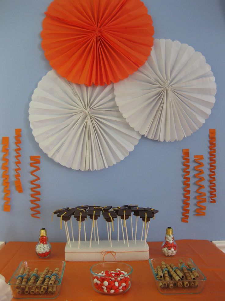 Cute backdrop decoration, graduation cap candies, and cookie diplomas for a graduation party
