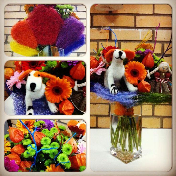 Яркий детский букет с разноцветными герберами и веточками, с маленькими зелеными хризантемками, физалисом и игрушками на каркасе из сизаля в виде цветика-семицветика.