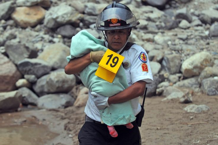 TRAGIC ACCIDENT: A firefighter carried the body of a child killed in a bus accident on Monday in San Martin Jilotepeque, Guatemala. A bus plunged down a steep cliff in western Guatemala killing at least 43 people and injuring 40 others, firefighters said. (Johan Ordonez/AFP/Getty Images)