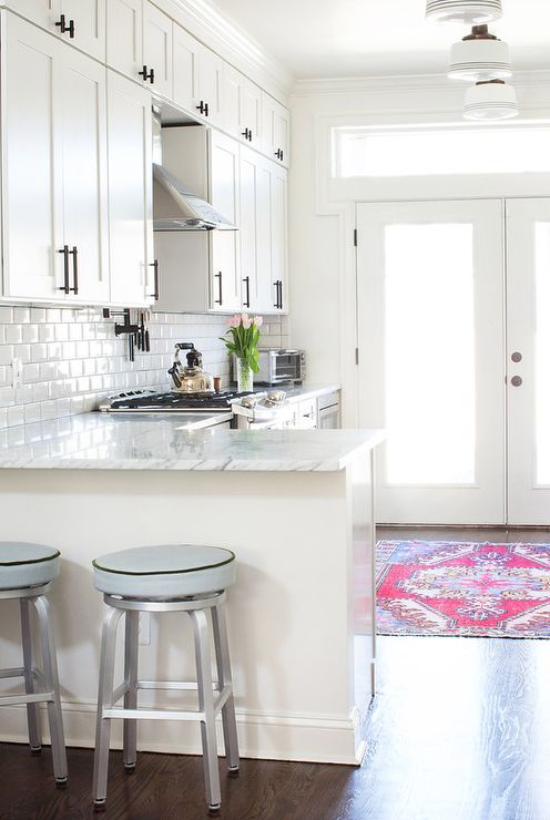 L-shaped white marble kitchen countertops form a peninsula seating Crate & Barrel Spin Swivel Backless Counter Stools illuminated by three striped schoolhouse pendants mounted to the ceiling in the center of the room.