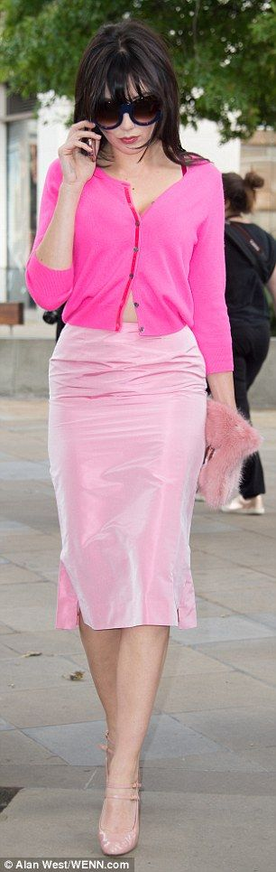 Va va voom:She left buttons on her neon pink cardigan undone to flash a hint of cleavage and her toned tum, teaming the knit with a high-waisted pencil skirt in a paler hue of pink