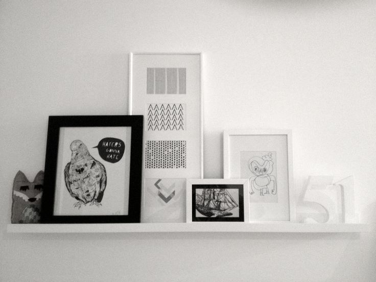 Ikea Ribba picture rail with various white and black frames and mounts and black and white sketches by Jamie Lawton, Jon Burgerman and pattern postcards from etsy