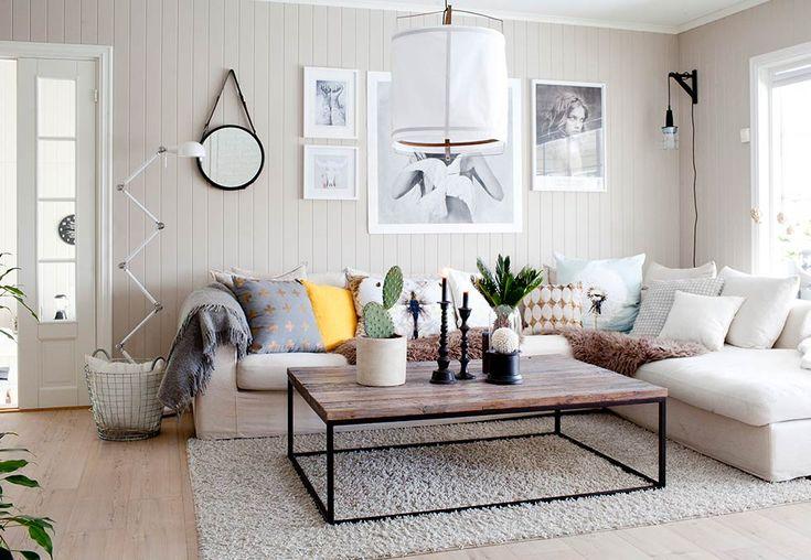 Salon w stylu skandynawskim z ogromną białą kanapą i poduszkami