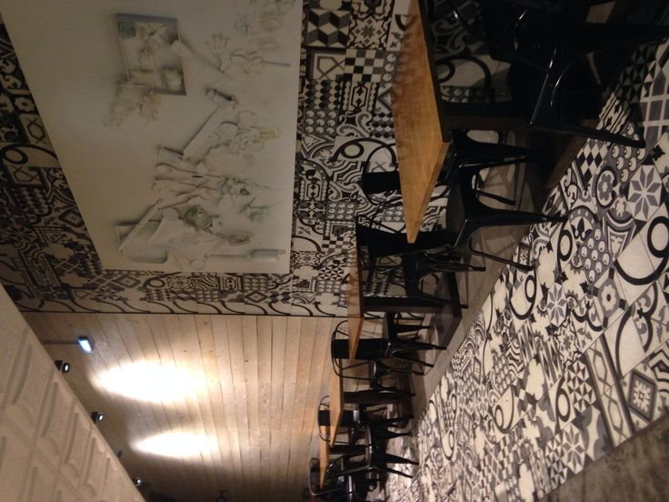 Monochrome patterned tiles add drama to this Greek restaurant