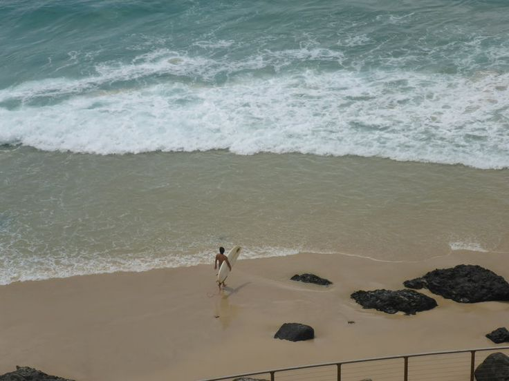 Kirra Beach - Gold Coast Australia. A lone surfer prepares to head out into the surf. Welcome to our travel blog! www.suchisaustralia.com