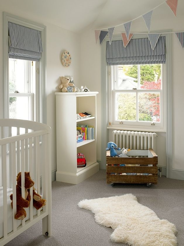 baby boy nursery, cot, bunting, roman blind. he children's bedrooms are designed for easy access to toys and books while keeping the bulk of the floor area empty. Kids like to play on the floor and in this room a comfortable sheepskin rug offers the perfect place to hang out on while the flags strung across the ceiling add in the vertical fun.