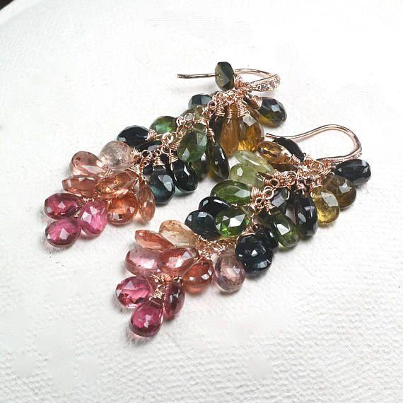Bella multi colore tormalina briolettes sono presenti in orecchini Mireya. Ho selezionato questi briolettes tormalina per mostrare una vasta gamma di colori della tormalina. Linizio di orecchini con tormalina verde foresta profonda nella parte superiore, seguita dalle sfumature gialle marrone, verde, verde acqua blu, rosa salmone e termina con tormalina rosa. Gli orecchini sono rifiniti con una coppia di CZ spianare Rose vermeil orecchio fili.  Componenti metallici utilizzati sono 14 k Rose…
