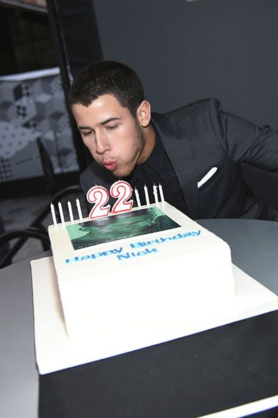 """September 16: Nick Jonas blows out candles on his 22nd birthday cake at the premiere for his music video """"Jealous"""" at South Street Seaport in New York City."""