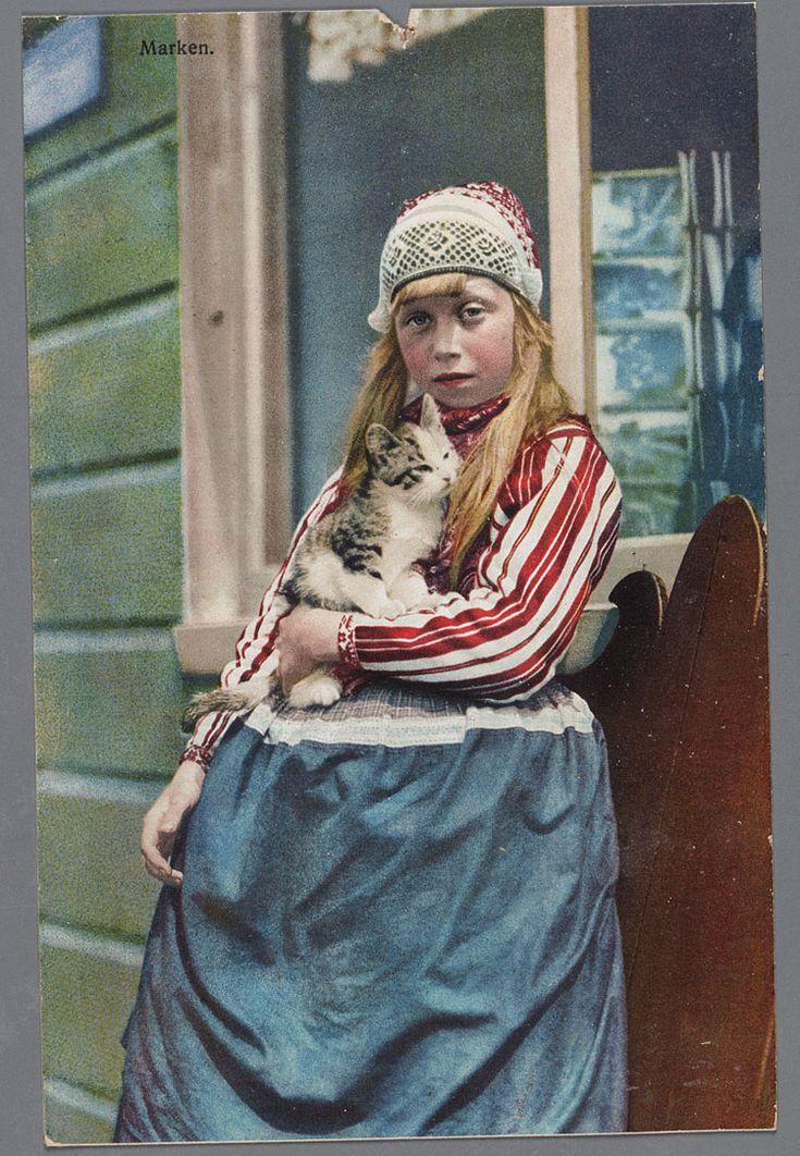 Marker meisje in klederdracht met jong poesje op de arm, voor de deuropening van een Marker huisje. 1900-1910 #NoordHolland #Marken
