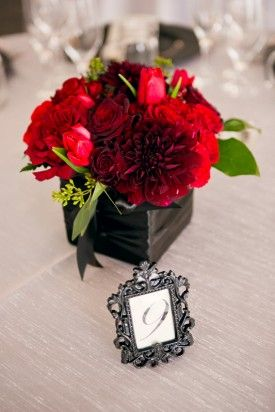 These bright red flowers look beautiful in a dark grey flower box for a wedding centerpiece.