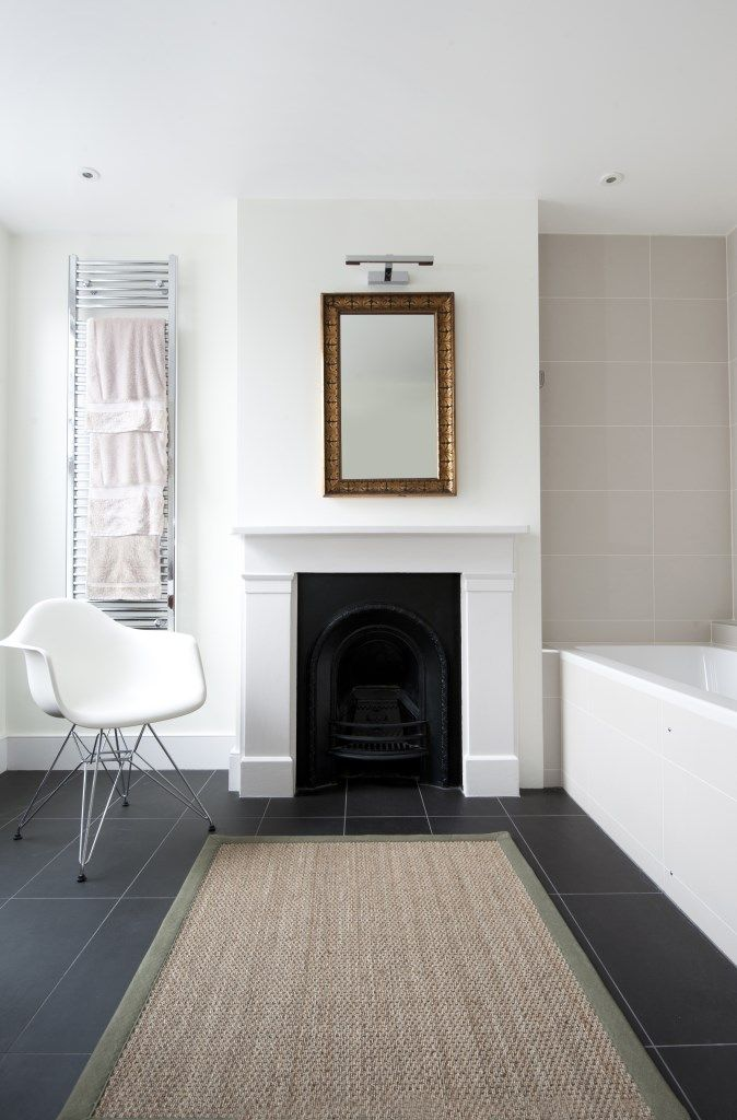 A period bathroom with a restored fireplace surround