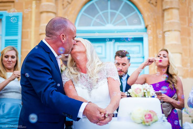 Bride and groom kissing after cutting their wedding cake at Villa Bologna, Malta.