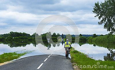 Cyclist on a flooded road in Loire valley. France
