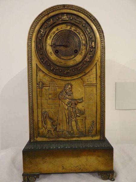 Antigo relógio em bronze dourado com figura de Arquimedes e seus livros. O curioso da peça é o mostr