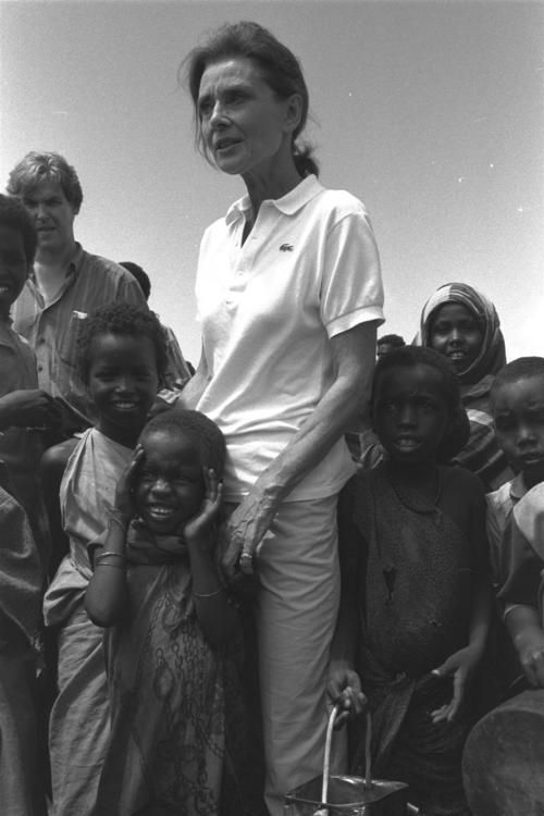 UNICEF Goodwill Ambassador Audrey Hepburn stands surrounded by children at a camp for displaced persons near the town of Kismayo, Somalia. 1992 © UNICEF/Betty Press. S)