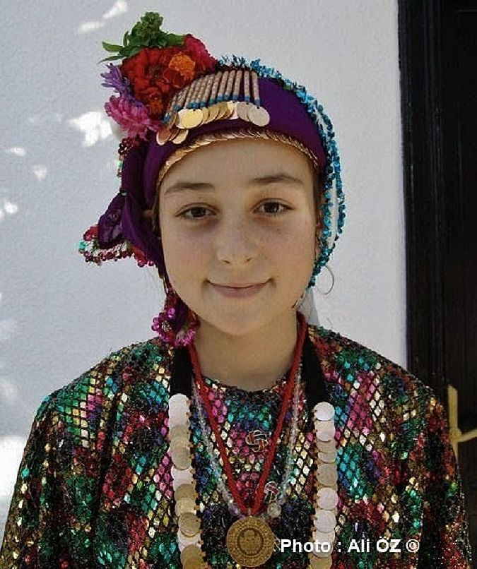 ÇOMAKDAĞ (near Milas, Muğla province): Yörük wedding. A touristic (close to authentic) event organised for tourists. A young girl in the festive traditional outfit of the village. The 'Yörük' are a Turkish group of people, some of whom are (semi-)nomadic, primarily inhabiting the mountains of Anatolia and partly Balkan peninsula.  Yörük maintain in general some association with nomadic life, are poorer (mostly) than average, and all of them are Sunni (unlike the Türkmen, who can be Alevi).