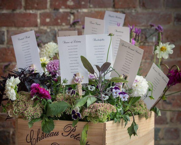 plan de table mariage esprit nature- plantes à fleurs et cartes dans un bac en bois