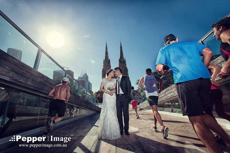 Runners passing by a wedding couple who are posing for bridal portrait in front of St Mary's Cathedral in Sydney.
