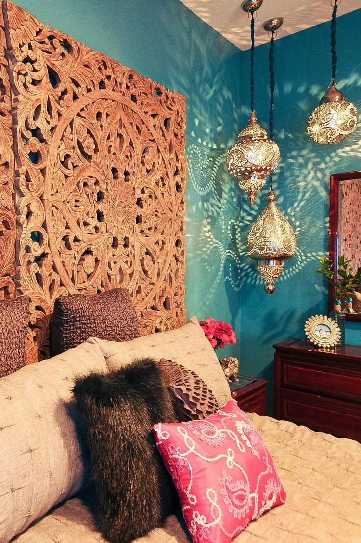 Rich teal walls, Moroccan lanterns and a dramatic headboard made from a pair of antique carved wooden panels makes this a vibrant retreat.