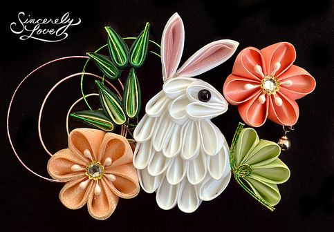 "Bunny In The Flower Garden Kanzashi - An adorable and unique bunny fashioned in tsumami kanzashi style stands like an inquisitive visitor in a spring garden, framed in beautiful, vibrant flowers and lush green foliage. Sparkling organza fabric, glittering gems, and bright mizuhiki accents in shades of green and pink give life to the piece, finished by a gently chiming bell detail. Mounted on an alligator clip for easy wear, this kanzashi measures approximately 5.25"" x 3.5""."
