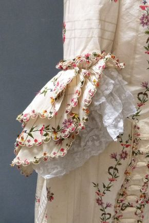 Detail sleeve, robe à la francaise, England (Spitalfield's), 1760s, remodeled 1780s. Ivory ground silk taffeta woven with a narrow self weave stripe, with gently curving flower and leaf meanders in puce, shaded tangerine flowerheads, red berries and sage green foliage, alternating with small sprays of flowers in deep rose pink and ivory. Trimmed with same tufted silks and corded wire loops.