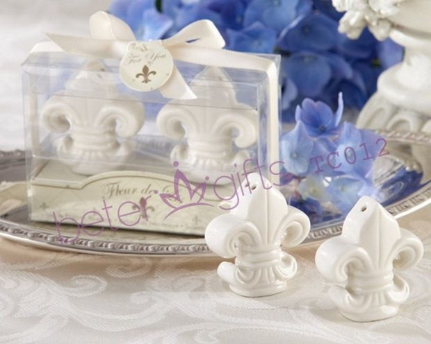 """Fleur-de-Lis"" Ceramic Salt & Pepper Shakers Perfect for the day you marry your knight in shining armor! Our fleur-de-lis salt and pepper shakers wedding favor brings a touch of nobility to your tables and helps create the elegant ambiance you imagine for your wedding design. Details: Stunning set of beautifully detailed, white-ceramic, fleur-de-lis-inspired salt and pepper shakers; gift presentation includes clear display gift box, cream-colored base"